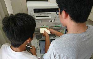 ゆうちょ銀行のATMで貯金をする子ども